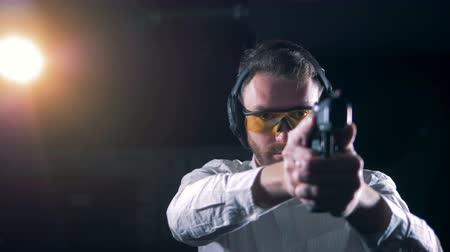A shooter aims with a pistol at a shooting range, close up.
