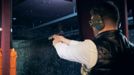 A person practices at a shooting range, firing a gun, close up.