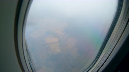 View on a land from a flying plane in clouds. 影像素材