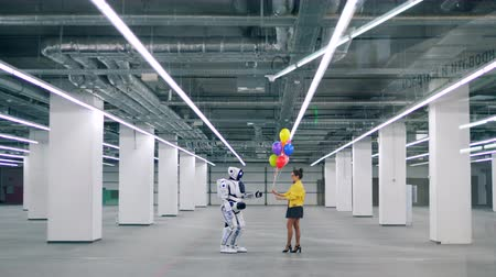 Young woman gives colorful balloons to a white robot.