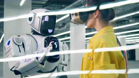 Young woman touches robots hand while wearing modern VR glasses.
