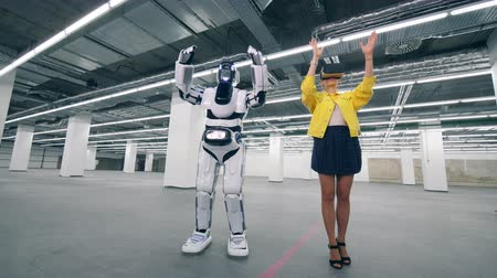 Woman in VR glasses controls a droid, moving arms. 影像素材