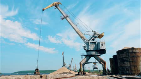 Big crane moves crushed stones, stocking them in a pile. Filmati Stock