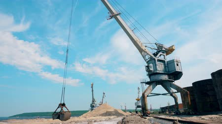 Metal crane moves crushed stones, working at docks.