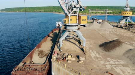 High crane with a bucket lifting breakstones from a barge. Filmati Stock