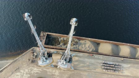 Modern cranes work at docks, moving breakstones from a barge.