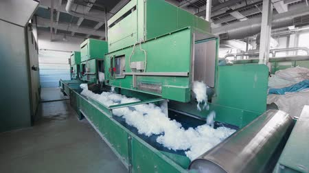 Plant machines push synthetic fiber onto a long conveyor.