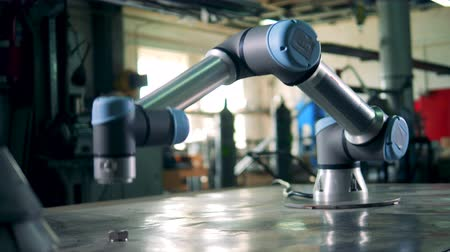 Cybernetic arm moving on a table at a modern factory.