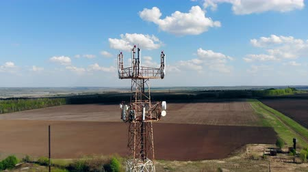 Long tower with cellular antennas in a field. Filmati Stock