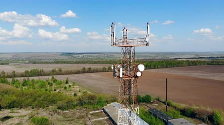 vysílač : Metal tower transmitting cell signals on a field.