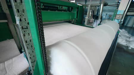 spool : Industrial conveyor rolls synthetic fabric into a spool.