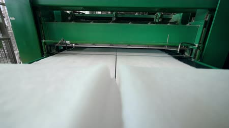 sentetik : Factory machine spooling white fabric on a conveyor.