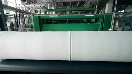 sentetik : Synthetic material coiled in spools on a factory conveyor.