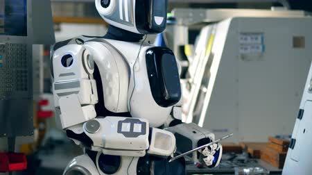 navigating : Human-like droid is operating a tablet in a factory unit