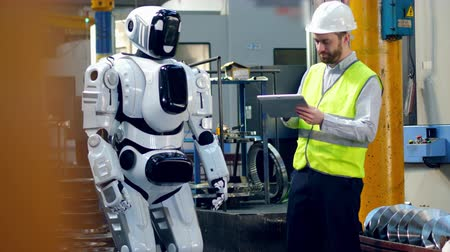 switching : Tall robot is being launched by the male worker Stock Footage