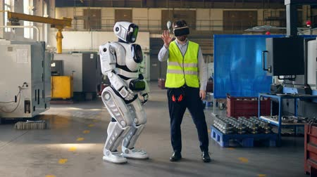 functioning : Human-like droid is moving under control of the worker in VR-glasses Stock Footage