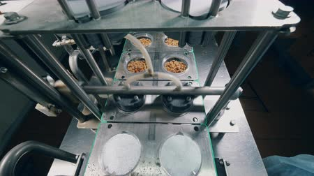 migalhas : Industrial mechanism is putting foil onto plates with bread crumbs