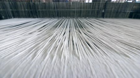 ruhakészítés : Industrial textile factory. Close up of thick white threads moving through the loom