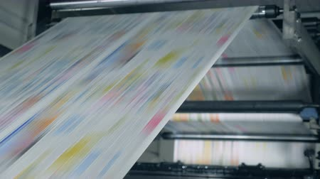 mechanically : Colour-printed paper is rolling through the polygraphic mechanism. Fake news concept. Stock Footage