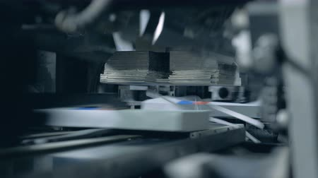 üreten : Industrial machine is processing printed books