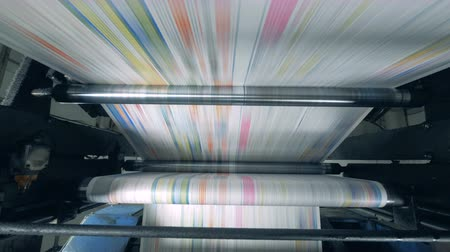 mechanically : Printing press releasing solid piece of coloured paper