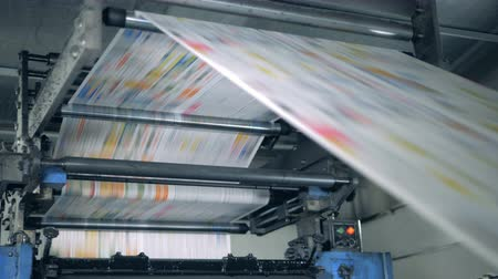 front cover : Publishing house unit with paper rolling through the machine. Printing newspapers in typography.