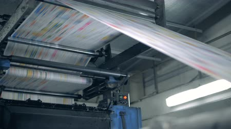 nakladatelství : Coloured paper page is moving through the typographic press. Printing newspapers in typography.