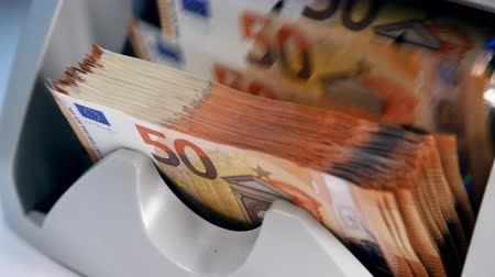 euro banknotes : Person uses counting device to check printed euros.