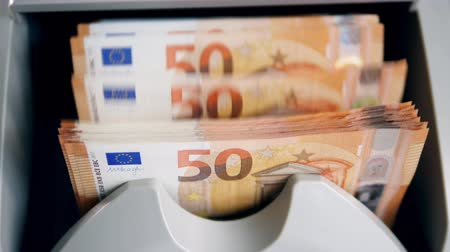pushed : Many euro banknotes pushed in a money counter while checking.