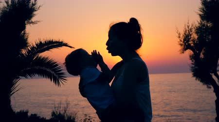gently : Family, love, tenderness concept. A kid and his mother playing on a beach on a sunset background.
