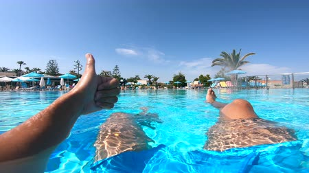 à beira da piscina : Person gives a thumbs up while sitting in a pool near hotel. Summer vacation concept. Vídeos