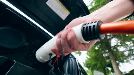 foglalat : Man removes charging cable from a electric car socket. Charging of electric car.