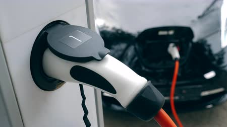 foglalat : Charging of electric car. White electromobile charger plugged to a rack socket.