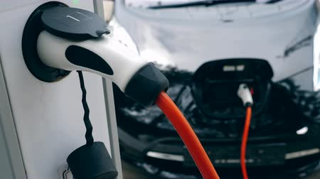douille : White charger works with electromobile, recharging it. Innovative electric hybrid car charging.