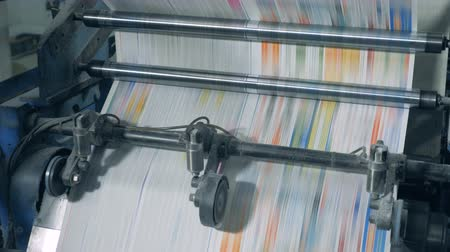 ヘッドライン : Dyed paper is rapidly moving through the printing mechanism. Printing newspapers in typography. 動画素材