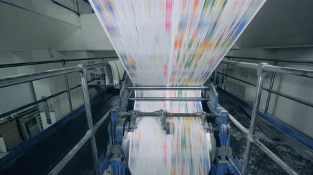 mechanically : Polygraphic machine is rolling colour-printed paper