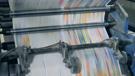 front cover : Printing newspapers in typography. Rapid motion of coloured paper through the typographic mechanism