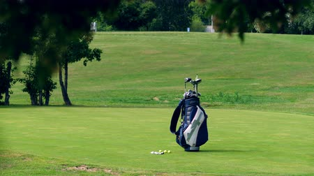 golfjátékos : A bag with golf accessories in the middle of the field Stock mozgókép