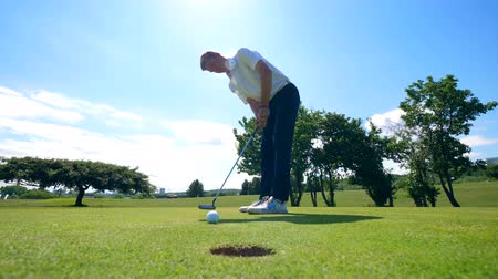 golfjátékos : The golf ball is falling into the hole after getting hit by the man Stock mozgókép
