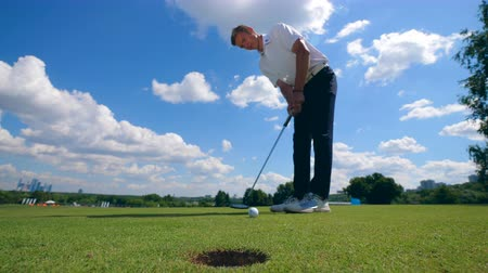 skillful : Golf ball is missing the hole after mans hit Stock Footage