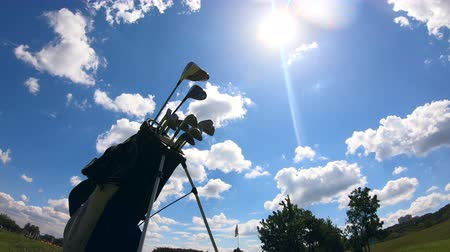 stacked : Golf clubs with sky in the background timelapse Stock Footage