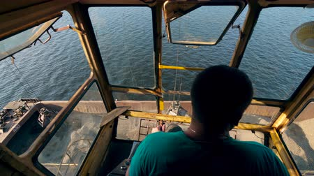 estaleiro : Man operates a crane to unload crushed stones from a barge. Vídeos