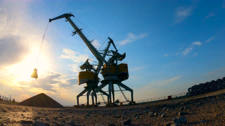 power equipment : Process of breakstones unloading on a sunset background.