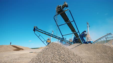 macchine movimento terra : Crushed stone moving on a line of a crushing machine. Mining industry equipment.
