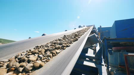 pedreira : Rubble moving on a conveyor of a crusher. Mining industry equipment.