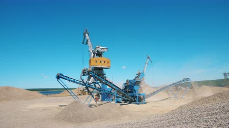 добыча : Crushing machine and a crane work with breakstones. Industrial mining concept.