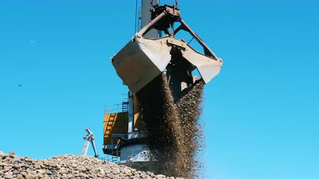 pedreira : Yellow crane carries rubble in a metal bucket. Industrial mining concept.