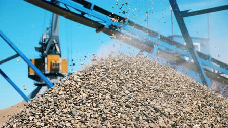 minério : A pile of crushed stone near a crushing machine. Industrial mining concept. Vídeos