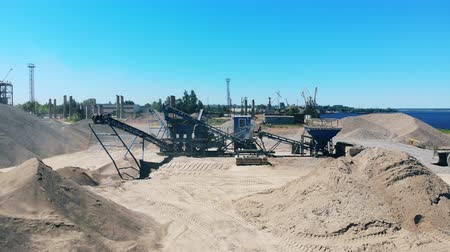 důl : Big crushing machine works at a quarry near water. Industrial mining concept.