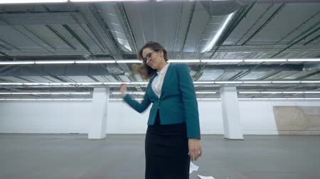 販売員 : Happy businesswoman having fun. Lady in a suit is dancing after throwing papers in an empty hall